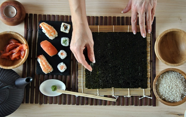 Mani che cucinano sushi con riso, salmone e nori