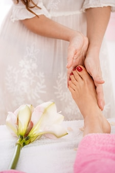 Mani che danno massaggio ai piedi lavorando in un salone luminoso e piacevole