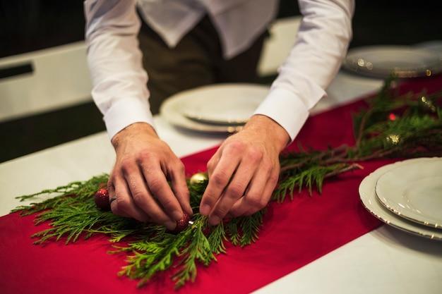 Mani che decorano la tavola con rami di abete e palline