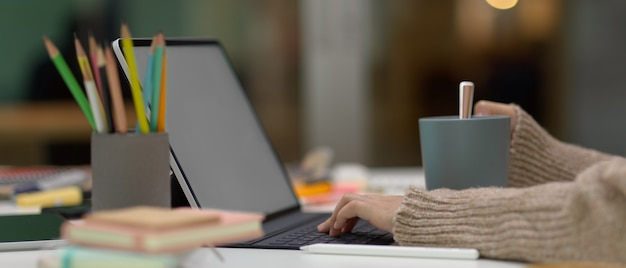 Mani che digitano sulla tastiera del computer portatile alla scrivania