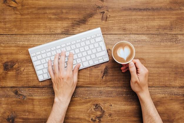 Mani che digitano sulla tastiera e che tiene caffè