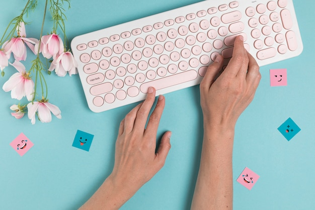 Mani che digitano sulla tastiera rosa
