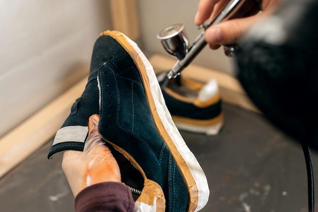 Mani che dipingono su un paio di scarpe