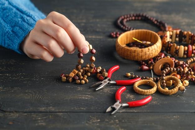 Mani che fanno gli orecchini di legno artigianali, fine in su