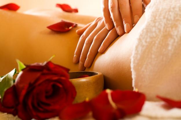 Mani che fanno massaggio alla schiena