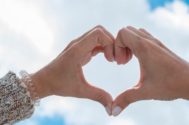 Mani che formano un cuore verso il cielo
