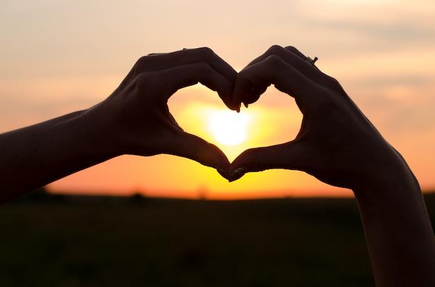 Mani che formano una forma di cuore in tempo tramonto
