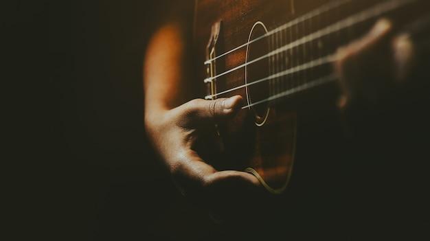 Mani che giocano la chitarra acustica delle ukulele. spettacolo di abilità musicali