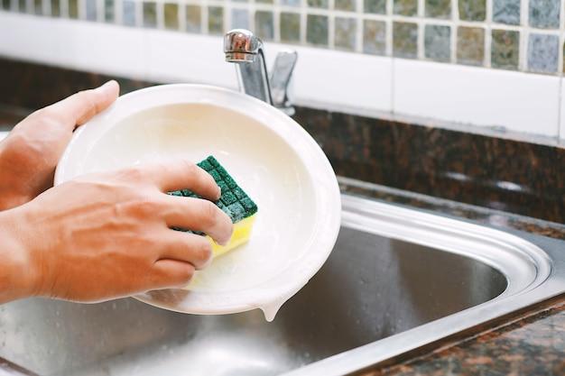 Mani che lavano i piatti con il cucchiaio