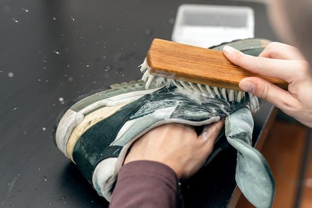 Mani che lavano le scarpe da ginnastica con un pennello