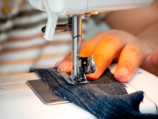 Mani che lavorano alla macchina da cucire