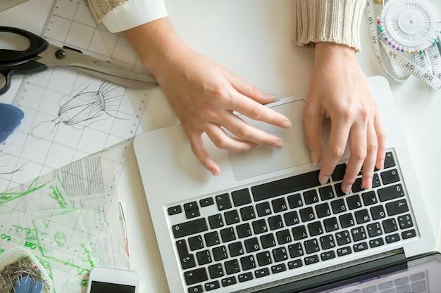 Mani che lavorano con un computer portatile, accessori per cucire in giro