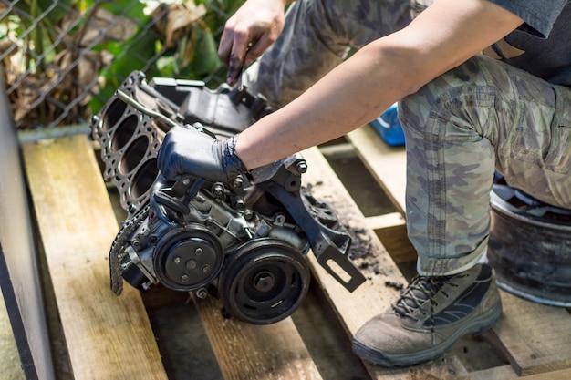 Mani che lavorano in un motore di automobile. pulizia del motore di un'auto. officina meccanica