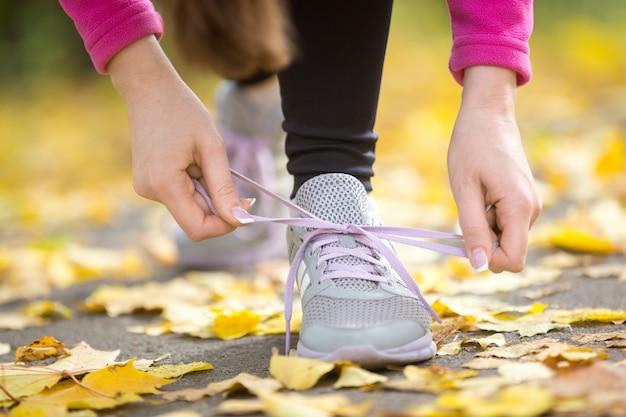 Mani che legano i calzoni dei formatori all'aperto di autunno