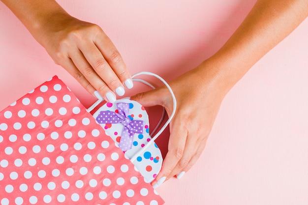Mani che mettono il contenitore di regalo nel sacchetto di carta