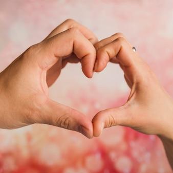 Mani che mostrano il segno del cuore