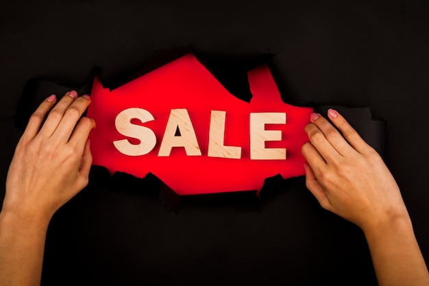 Mani che mostrano la parola di vendita attraverso la carta nera