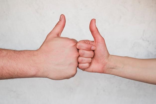 Mani che mostrano pollice sul segno