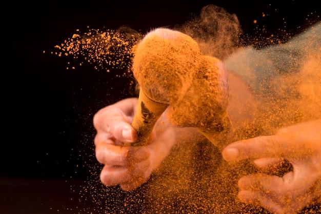 Mani che muovono pennelli cosmetici in nuvola di polvere arancia su sfondo scuro