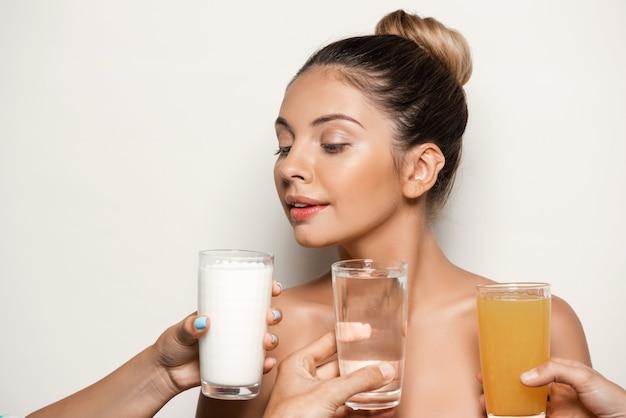 Mani che offrono acqua, succo o latte alla bella donna