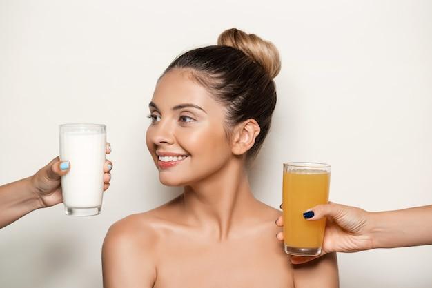 Mani che offrono succo o latte alla giovane bella donna