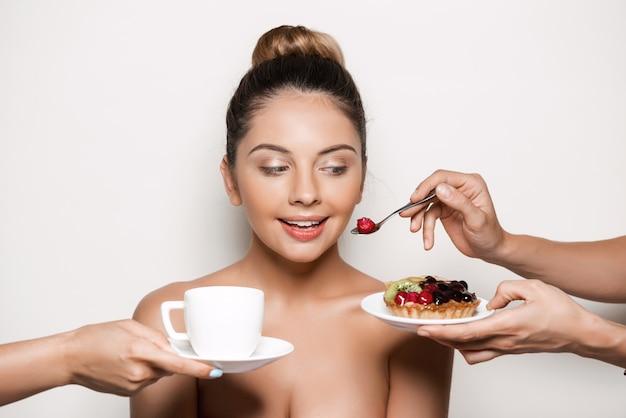 Mani che offrono torta e bevande a giovane bella donna