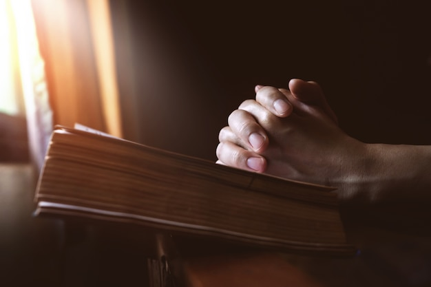 Mani che pregano sulla bibbia santa accanto a una luce di finestra