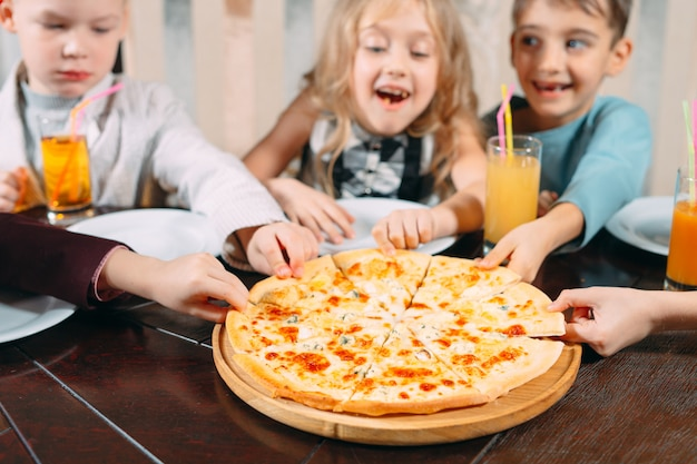 Mani che prendono le fette della pizza dalla tavola di legno, vista alta vicina.