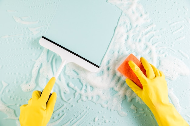 Mani che puliscono la finestra