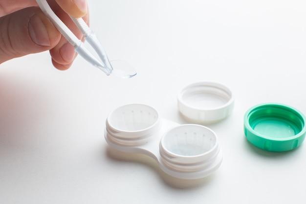 Mani che raccolgono una lente a contatto con pinzette e materiale di manutenzione per lenti a contatto sul tavolo bianco