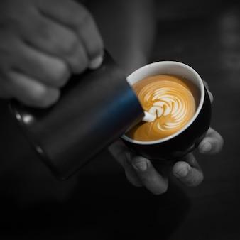 Mani che riempiono una tazza di caffè con latte
