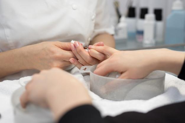 Mani che rimuovono le cuticole con lo strumento per unghie professionale