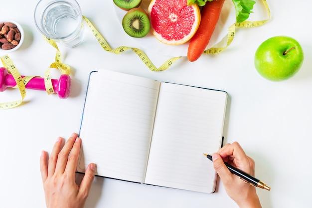 Mani che scrivono sul taccuino con frutta, verdura, manubri, metro a nastro e acqua. mangiare pulito ed esercizio fisico per il concetto di buona salute. alimenti biologici, concetto di dieta. vista dall'alto,