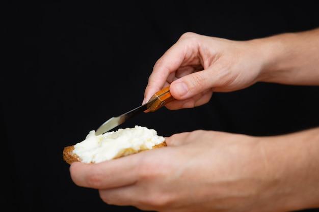 Mani che spalmano formaggio a pasta molle su pane tostato