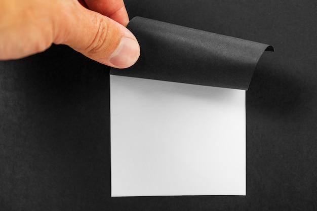 Mani che strappano un buco nella carta nera con bordi strappati