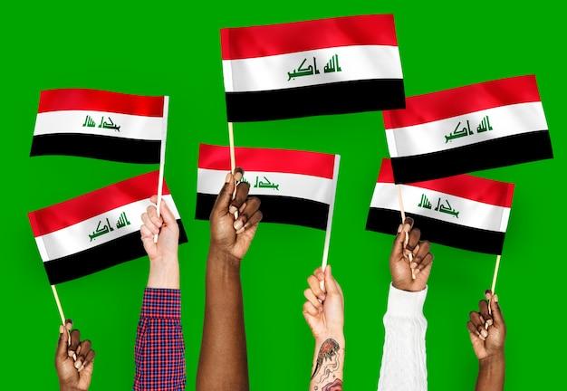 Mani che sventolano bandiere dell'iraq