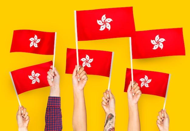 Mani che sventolano bandiere di hong kong