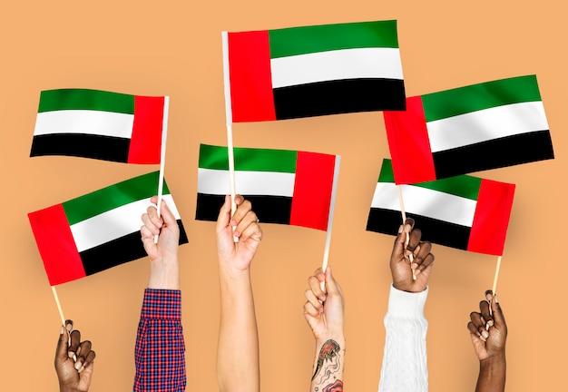 Mani che sventolano le bandiere degli emirati arabi uniti