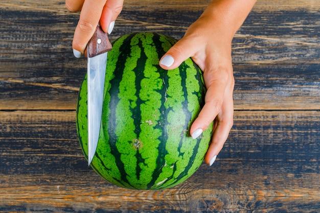 Mani che tagliano anguria con coltello