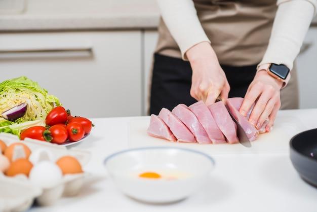 Mani che tagliano carne cruda sul tavolo
