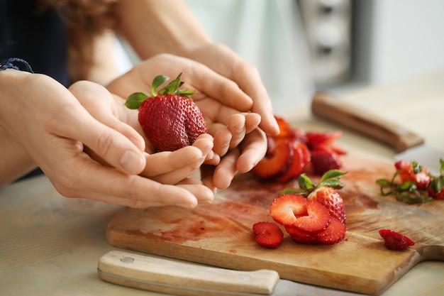 Mani che tagliano le fragole fresche