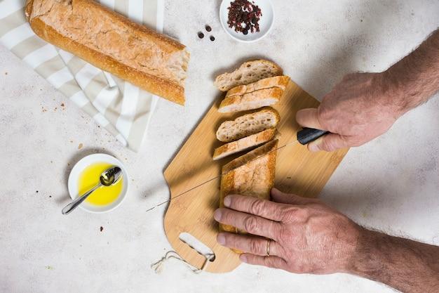 Mani che tagliano pagnotte di pane