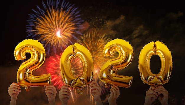 Mani che tengono 2020 palloncini numeri con sfondo di fuochi d'artificio