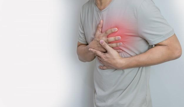 Mani che tengono al torace con malattia di sintomo di attacco di cuore