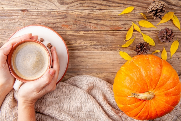 Mani che tengono caffè caldo su fondo di legno con la zucca
