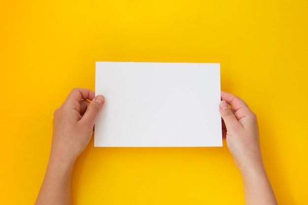 Mani che tengono carta bianca vuota, vuota isolato su giallo con lo spazio della copia