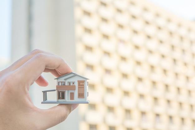 Mani che tengono casa. immobiliare e concetto di proprietà.