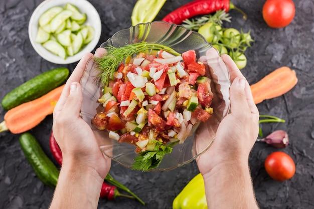 Mani che tengono ciotola di insalata con fondo vago