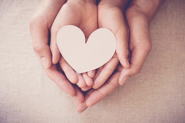 Mani che tengono cuore bianco, assicurazione sanitaria cuore, carità di donazione, concetto di bambino adottivo