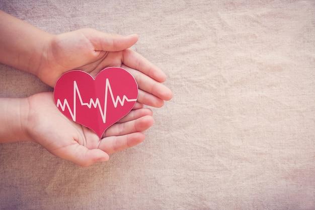 Mani che tengono cuore rosso con cardiogramma